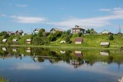 Russisches Norddorf Isady Sommertag, Emca-Fluss, alte Häuschen auf dem Ufer, alte Holzbrücke und Wolkenreflexionen Stockbilder