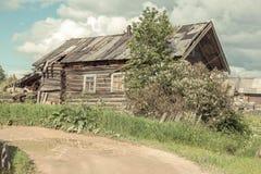 Russisches Norddorf Isady Sommertag, Emca-Fluss, alte Häuschen auf dem Ufer, alte Holzbrücke Verlassenes Gebäude Lizenzfreies Stockbild