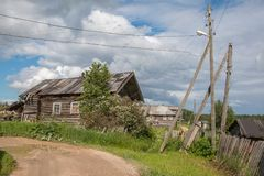 Russisches Norddorf Isady Sommertag, Emca-Fluss, alte Häuschen auf dem Ufer, alte Holzbrücke Verlassenes Gebäude Stockbild