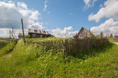 Russisches Norddorf Isady Sommertag, Emca-Fluss, alte Häuschen auf dem Ufer, alte Holzbrücke Verlassenes Gebäude Lizenzfreies Stockfoto