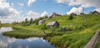 Russisches Norddorf Sommertag, Fluss, alte Häuschen auf Küste Stockfotografie