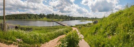 Russisches Norddorf Sommertag, Fluss, alte Häuschen auf Küste Stockfoto