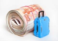 Russisches Papiergeld rollte oben nahe bei einem kleinen Reisekoffer stockfotos