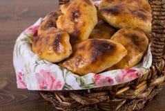 Russisches pirozhki (gebackene Pastetchen) im Korb auf Holztisch Lizenzfreie Stockbilder