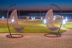 Russland, Bolgar - 8. Juni 2019 Kol Gali Resort Spa: Zwei hängende geflochtene Stühle des Rattans gegen das Meer lizenzfreies stockbild