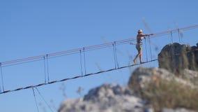 Russland, Krim, am 3. Juli 2017 Extreme junge Frau im Hut herein gehend auf das Seil auf langer hängender Brücke über dem Abgrund stock video footage