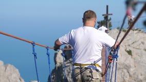 Russland, Krim, am 3. Juli 2017 Extremer Mann geht auf das Seil auf langer hängender Brücke über dem Abgrund in der Zeitlupe stock footage