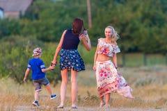 Russland, Merzhanovo: Am 22. August 2018: Ein Mädchen mit einem Kind macht ein Foto einer Freundin mit einem Smartphone im Wind lizenzfreie stockbilder