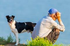 Russland, Merzhanovo, am 21. Mai 2018: Älterer Mann mit seinem Hund an der Sommerseeküste lizenzfreies stockfoto