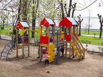 Russland, Saratow - 28. April 2019 Spielplatz mit farbigem Dia und hölzerne Gebäude auf der Straße stockfotografie