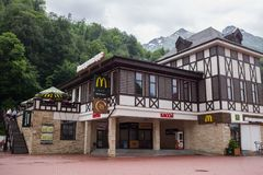 RUSSLAND, SOCHI - 25. MAI 2018: Redaktionelles Foto von McDonald-` s in Krasnaya Polyana, im Erholungsort gegen Berge lizenzfreie stockbilder