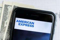 RUSSLAND, STR PETERSBURG, am 4. April 2019: Logo American Express Company in den Lügendiagrammen des Smartphone und in den Dollar stockfotografie