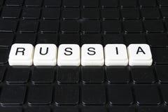 Russland-Textwortkreuzworträtsel Alphabetbuchstabe blockiert Spielbeschaffenheitshintergrund Schwarzer Hintergrund Stockbilder