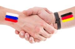 Russland- und Deutschland-Hände, die mit Flaggen rütteln Stockfotos