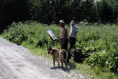 Russland - Usolye am 16. Juli 2017: alter Maler mit Farben der Bürste in der Hand auf Segeltuch in der Natur Stockbild
