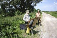 Russland - Usolye am 16. Juli 2017: alter Maler mit Farben der Bürste in der Hand auf Segeltuch in der Natur Lizenzfreie Stockbilder