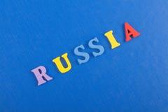 Russland-Wort auf dem blauen Hintergrund verfasst von den hölzernen Buchstaben des bunten ABC-Alphabetblockes, Kopienraum für Anz Lizenzfreies Stockfoto
