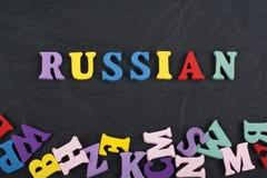 Russland-Wort auf dem schwarzen Bretthintergrund verfasst von den hölzernen Buchstaben des bunten ABC-Alphabetblockes, Kopienraum Lizenzfreies Stockbild