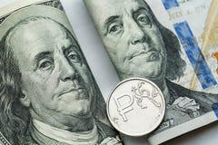 Russo le monete da una rublo e gli S.U.A. cento banconote del dollaro Fotografia Stock