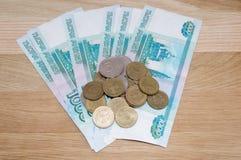 Russo 1000 rublos com moedas Fotografia de Stock Royalty Free