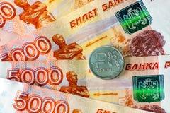 Russo una moneta della rublo e cinque mila rubli di banconote Fotografie Stock