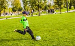 Russsia,Krasnodar,30 september 2018: boy on grass beats the ball. Boy on grass beats the ball Russsia,Krasnodar,30 september 2018 stock photo