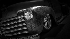 Rust American Muscle Hotrod. Rust american retro classic hotrod on black background with chrome grill and headlight and chrome rims Royalty Free Stock Photo