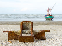 Rust anchor on the beach. And fishing boat background Royalty Free Stock Photos