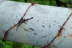 Rust barbed wire around pipe stock photos