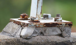 Rust base plate with rust bolt on broken concrete Royalty Free Stock Photo
