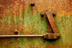 Rust, Bolts and Hinge. A detail shot of a rusted piece industrial equipment, showing a flat piece of metal with a few bolts and a hinge. Very textural with Stock Photos