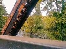 Rusted steel over river in fall. Rust covered bridge beams over fall river Stock Photos