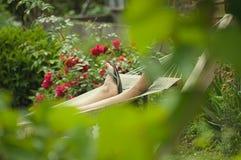 Rust in een hangmat onder rozen stock afbeeldingen