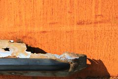 Rust on metal. Orange rust on corroded surface with devastated metal with shadow on it stock photo