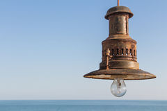 Rust never sleeps. Rusty fishing lamp on a blue sky with sea stock photography