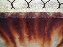 Rust stains on concrete. Bright rust stains on a wall beneath chain-link fence royalty free stock photo