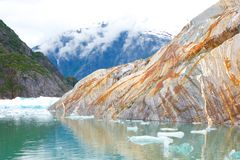 Rust Streaked Rock in Bay with Mountain and Icebergs Stock Images