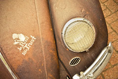 In Rust We Trust. Rusty old classic car with a sign of trust painted on the hood Stock Images