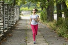 rustande parkkvinnabarn Morgonen joggar Sund livsstil royaltyfri foto