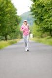 rustande parkväg som kör sportive kvinnabarn Arkivfoto