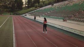 _ rustande sportflickaspring till och med stadion Ung kvinna som utomhus rustar stock video