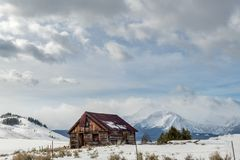 Rusted überdachte Blockhaus im Idaho-Wildniswinter mit clou Stockbild