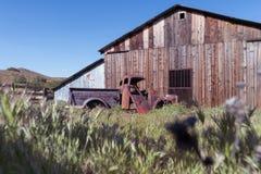 Rusted abandonó la camioneta pickup y el granero viejo Imágenes de archivo libres de regalías