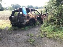 A rusted abandoned graffited car wreck royalty free stock images