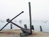 Rusted anchor. An anchor lies rusted at the harbor, in the background are many sailboat and small cabin cruisers Stock Photo