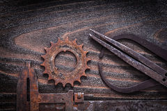 Rusted antique measuring calipers with gear wheel on vintage dar Royalty Free Stock Photos