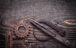 Rusted antique measuring calipers with gear wheel on vintage dar Royalty Free Stock Image