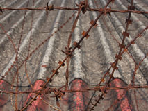 Rusted barbed wire  on the fence with roof background Stock Photo