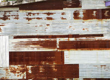 Rusted barn siding pattern. Corrugated metal white shed siding with brown rusty panels Stock Photo
