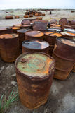 Rusted barrels on the shore, Chukotka, Russia. They remain from Soviet times Stock Photos